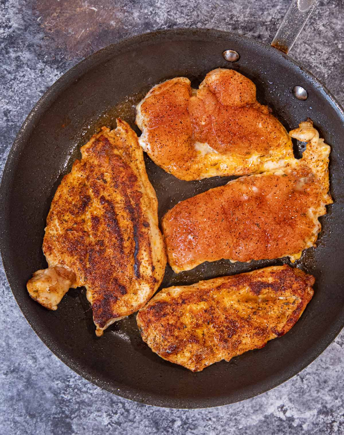 Blackened Chicken in frying pan, with two pieces cooked on top and two pieces uncooked on top