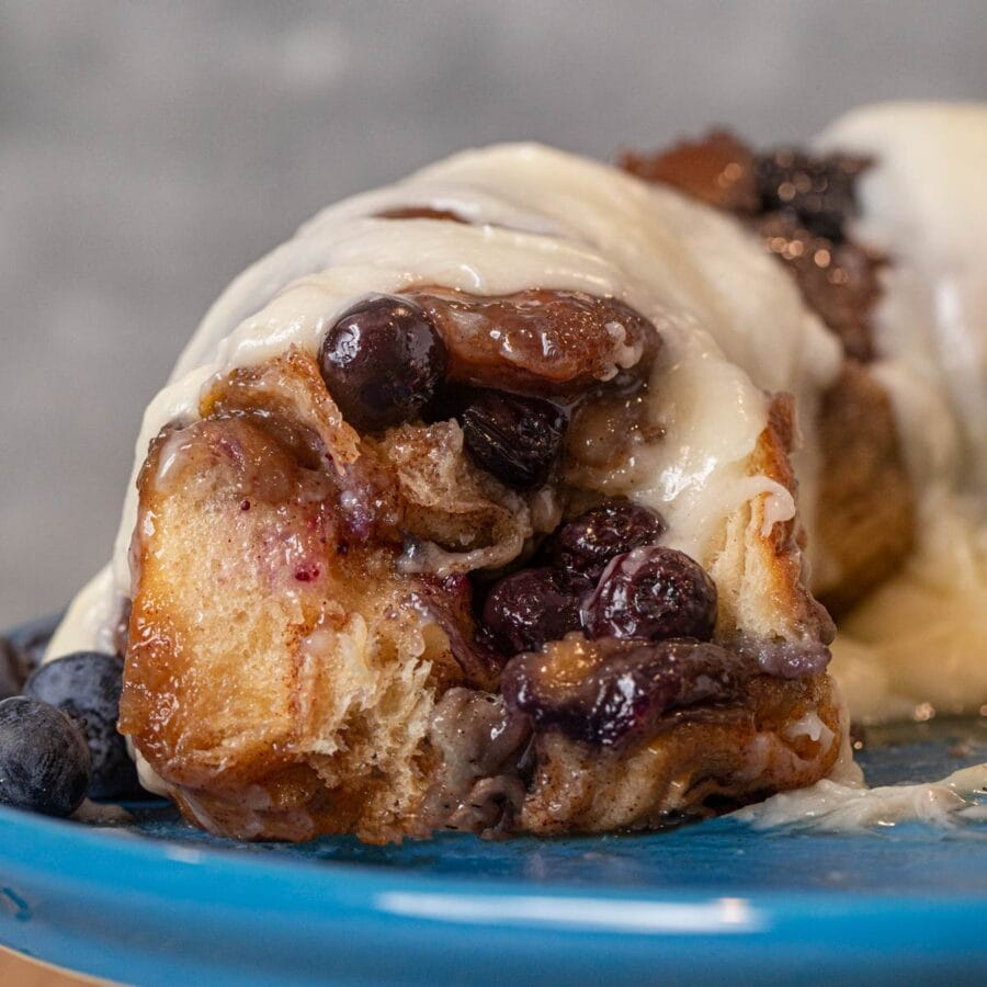 Blueberry Cream Cheese Monkey Bread with pieces removed on cake stand with icing