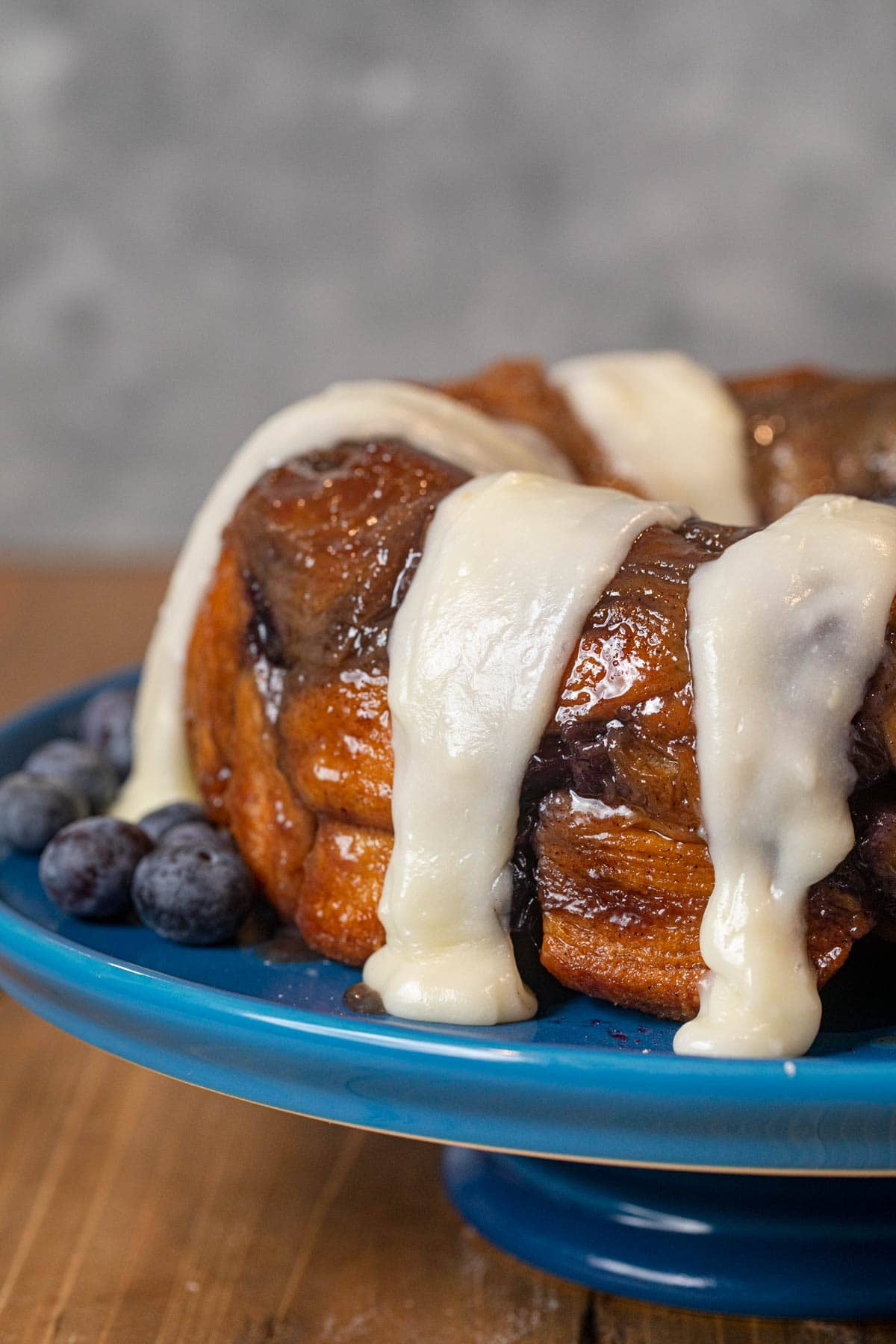 Blueberry Cream Cheese Monkey Bread on cake stand with icing