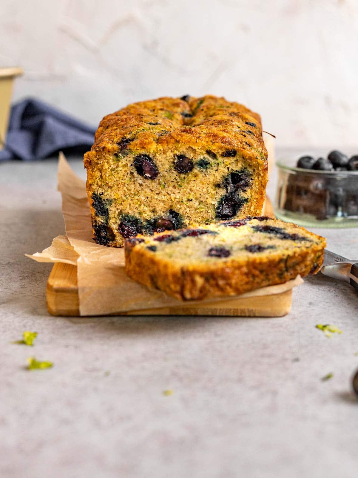 Blueberry Zucchini Bread loaf sliced on cutting board