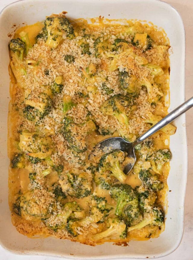 Cheesy Garlic Casserole in baking dish with spoon