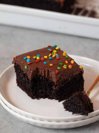 serving of Chocolate Sheet Cake on plate with bite on fork