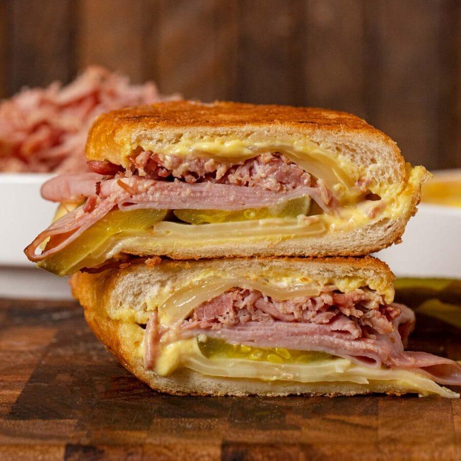 Cuban Sandwich halves stacked on cutting board