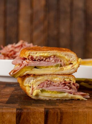 Cuban Sandwich halves stacked on cutting board