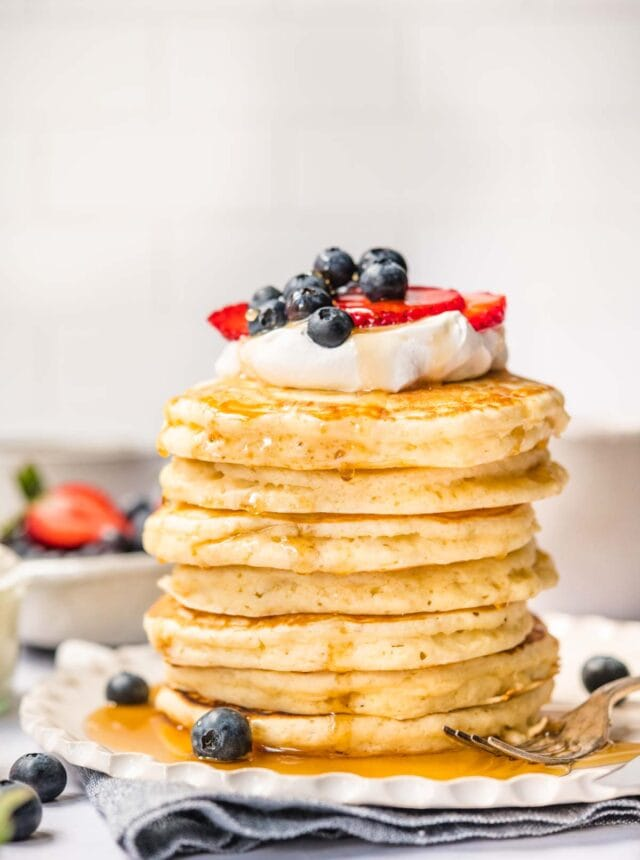 Perfect Fluffy Pancakes stacked on a plate with whipped cream, fresh berries, and maple syrup