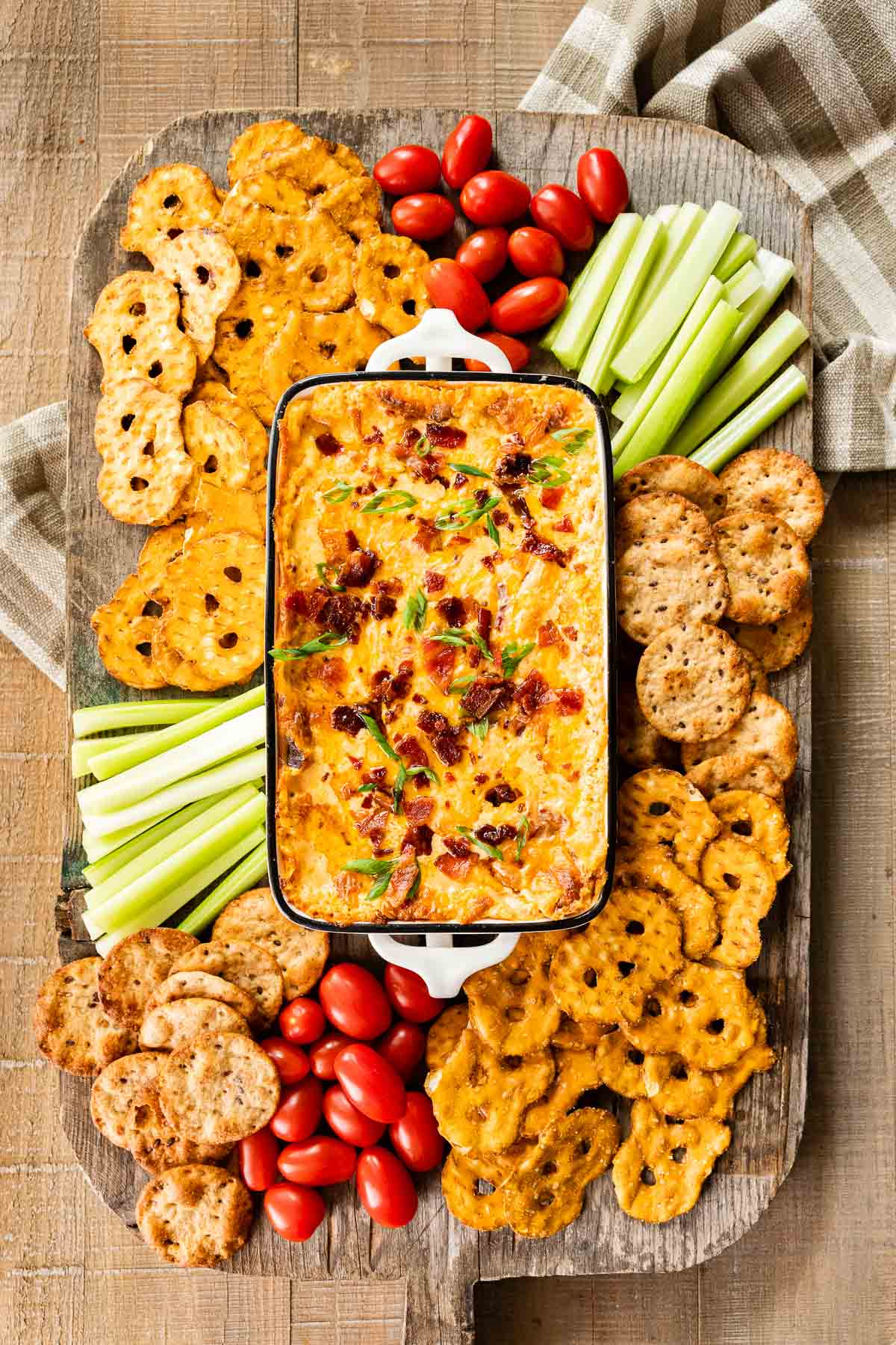 Hot Bacon Cheese Dip in baking dish with crackers and veggies