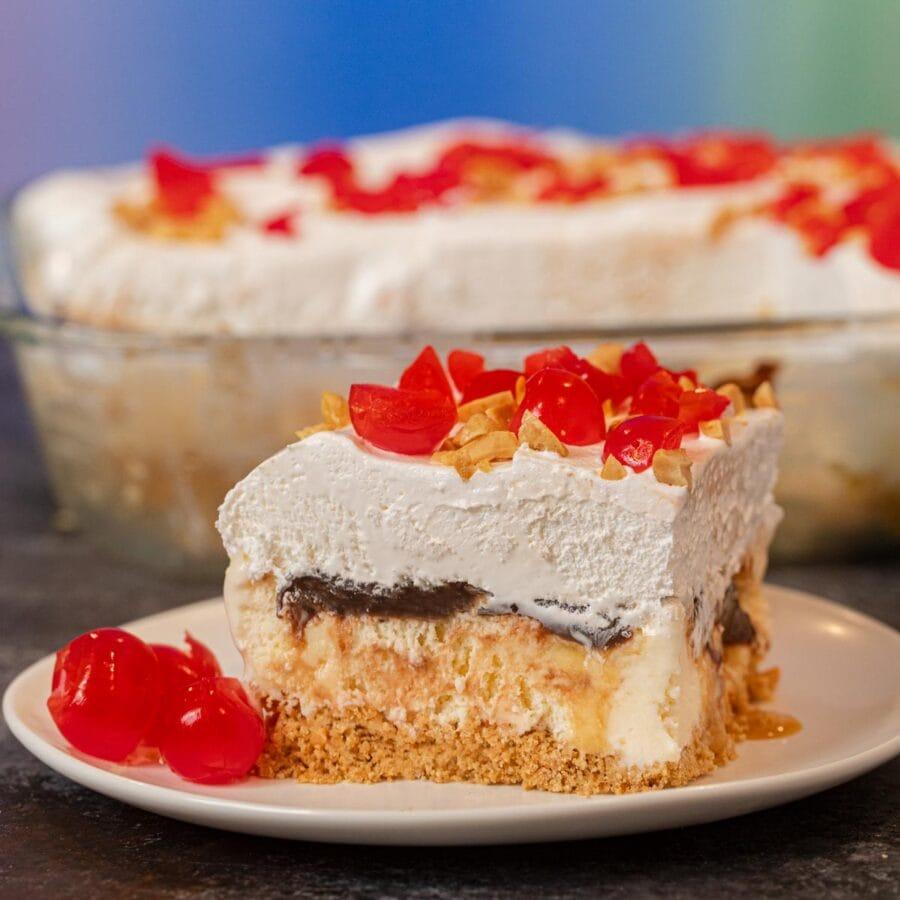 Ice Cream Sundae Casserole serving on plate with maraschino cherries