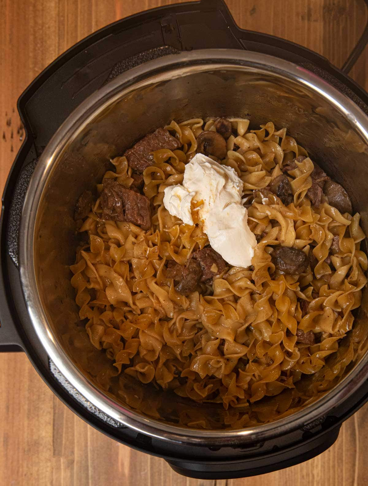 Instant Pot Beef Stroganoff and sour cream in pressure cooker