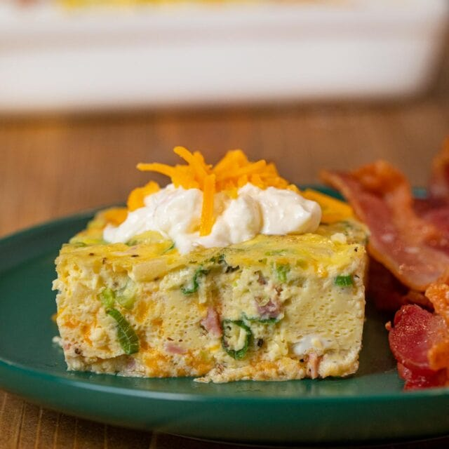 serving of Oven-Baked Omelette on plate with sour cream and bacon