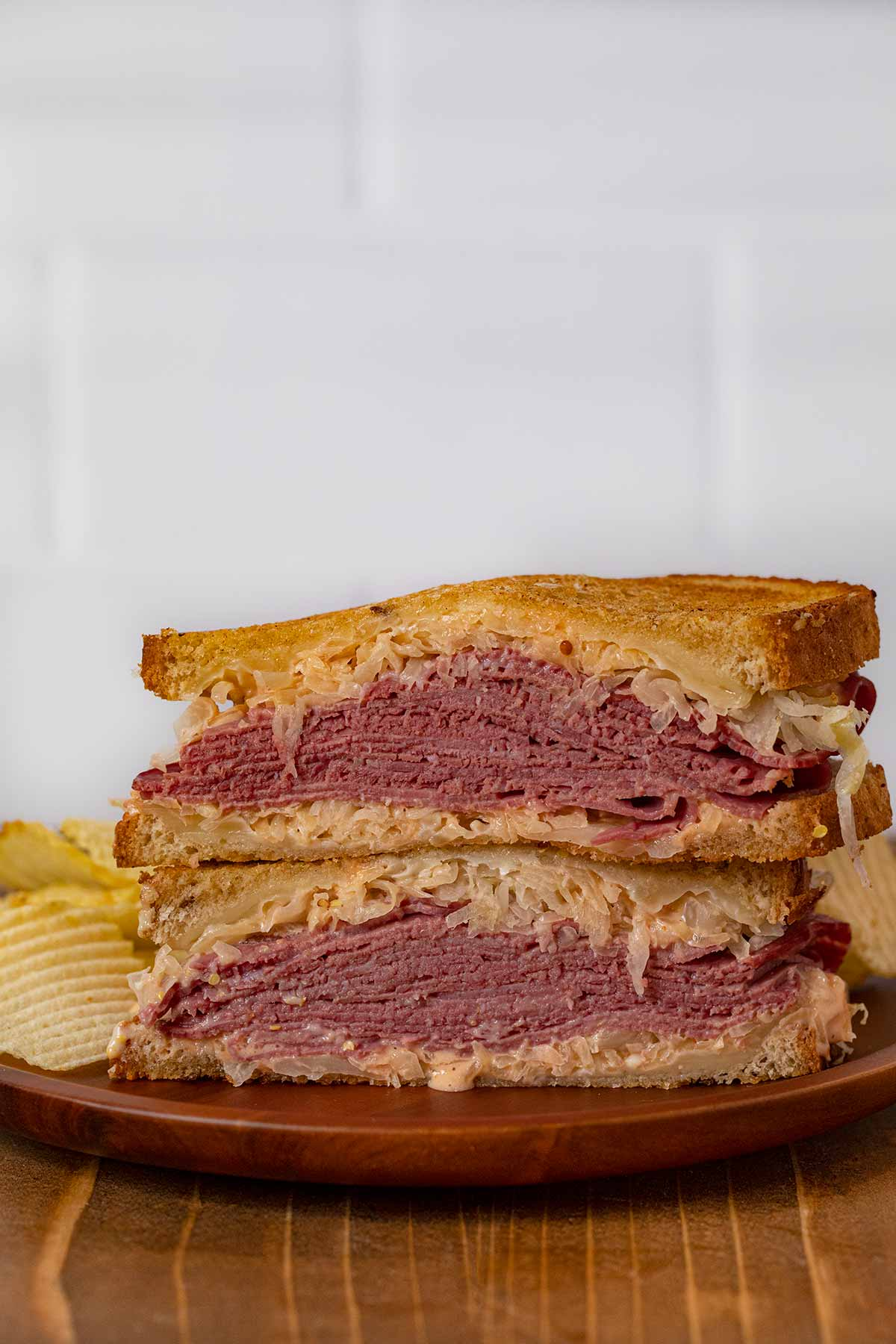 Reuben Sandwich halves in stack on plate with chips
