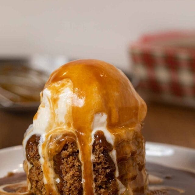 Sticky Toffee Pudding serving on plate with ice cream and sauce