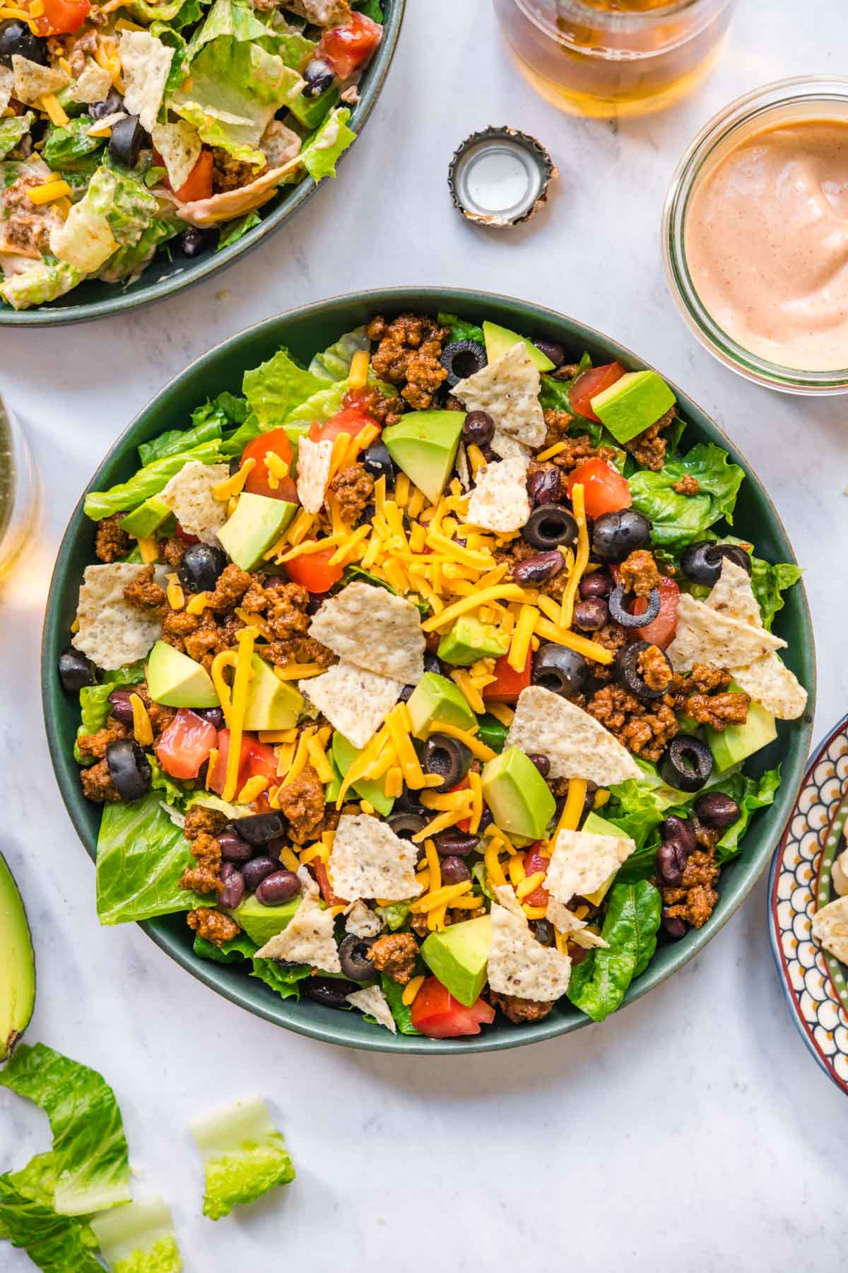 Assembled Taco Salad in bowl with lettuce, black beans, seasoned ground beef, shredded cheese, avocado.