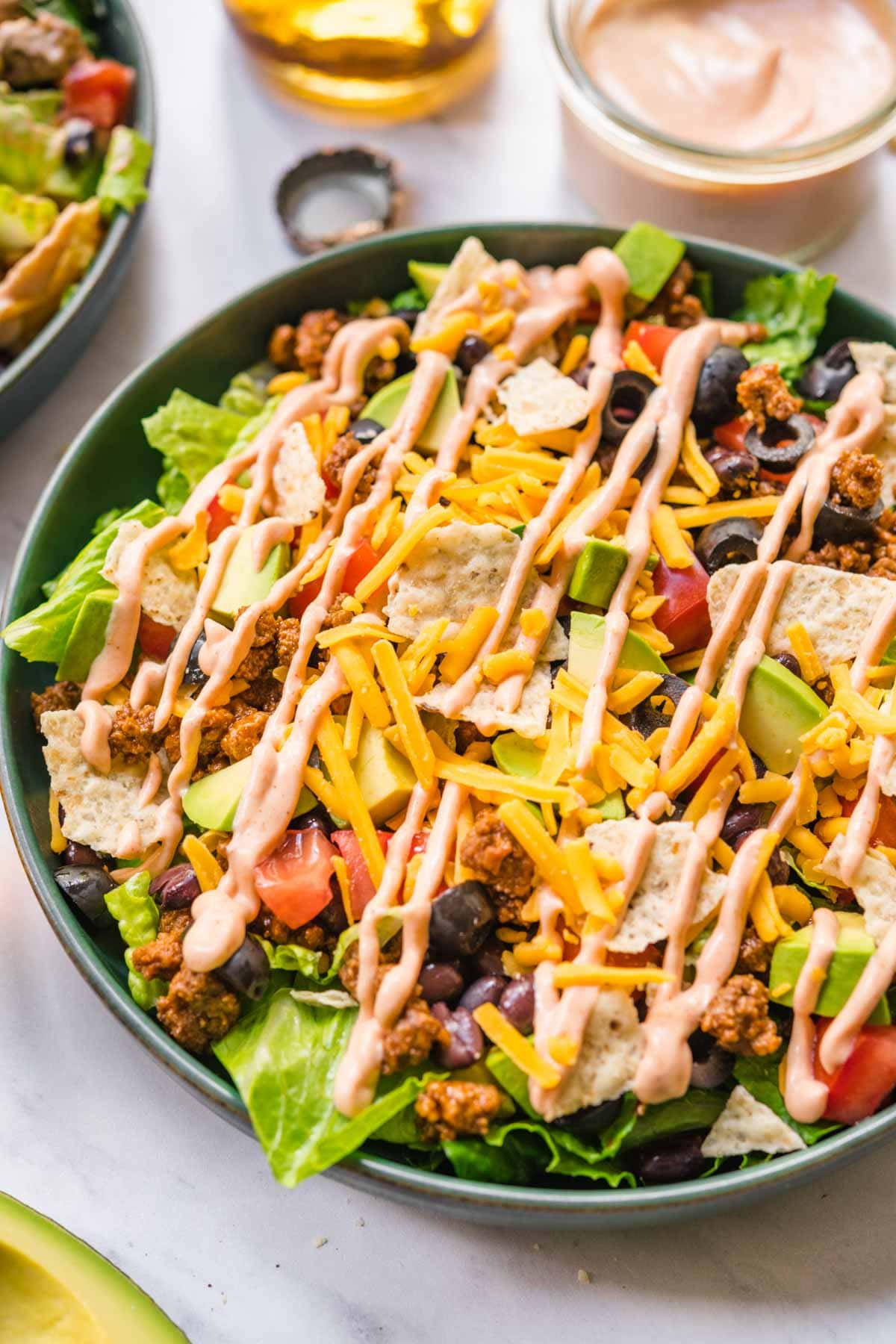 Assembled Taco Salad in bowl with lettuce, black beans, seasoned ground beef, shredded cheese, avocado, and dressing.