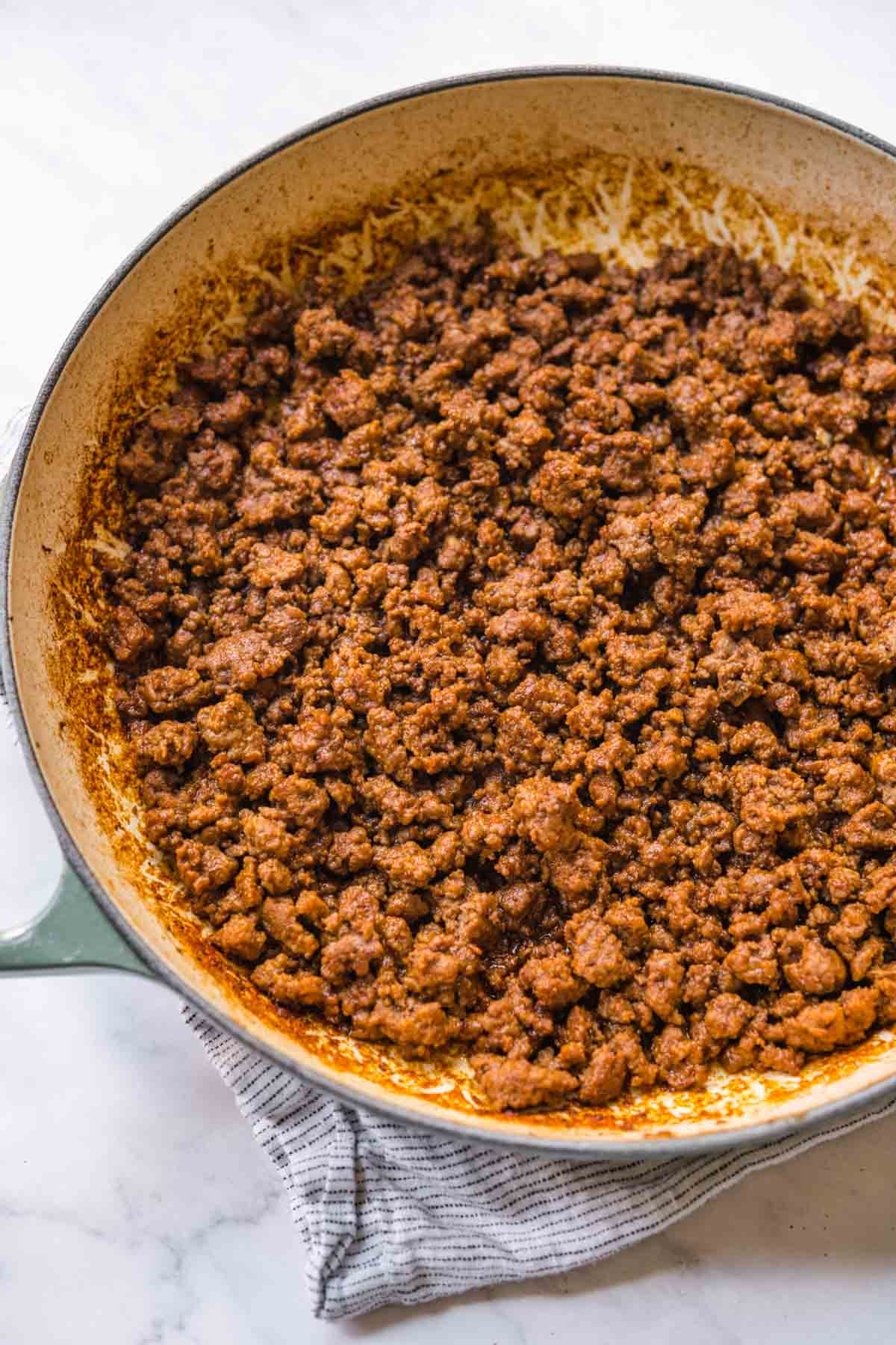Seasoned ground beef in skillet for Taco Salad