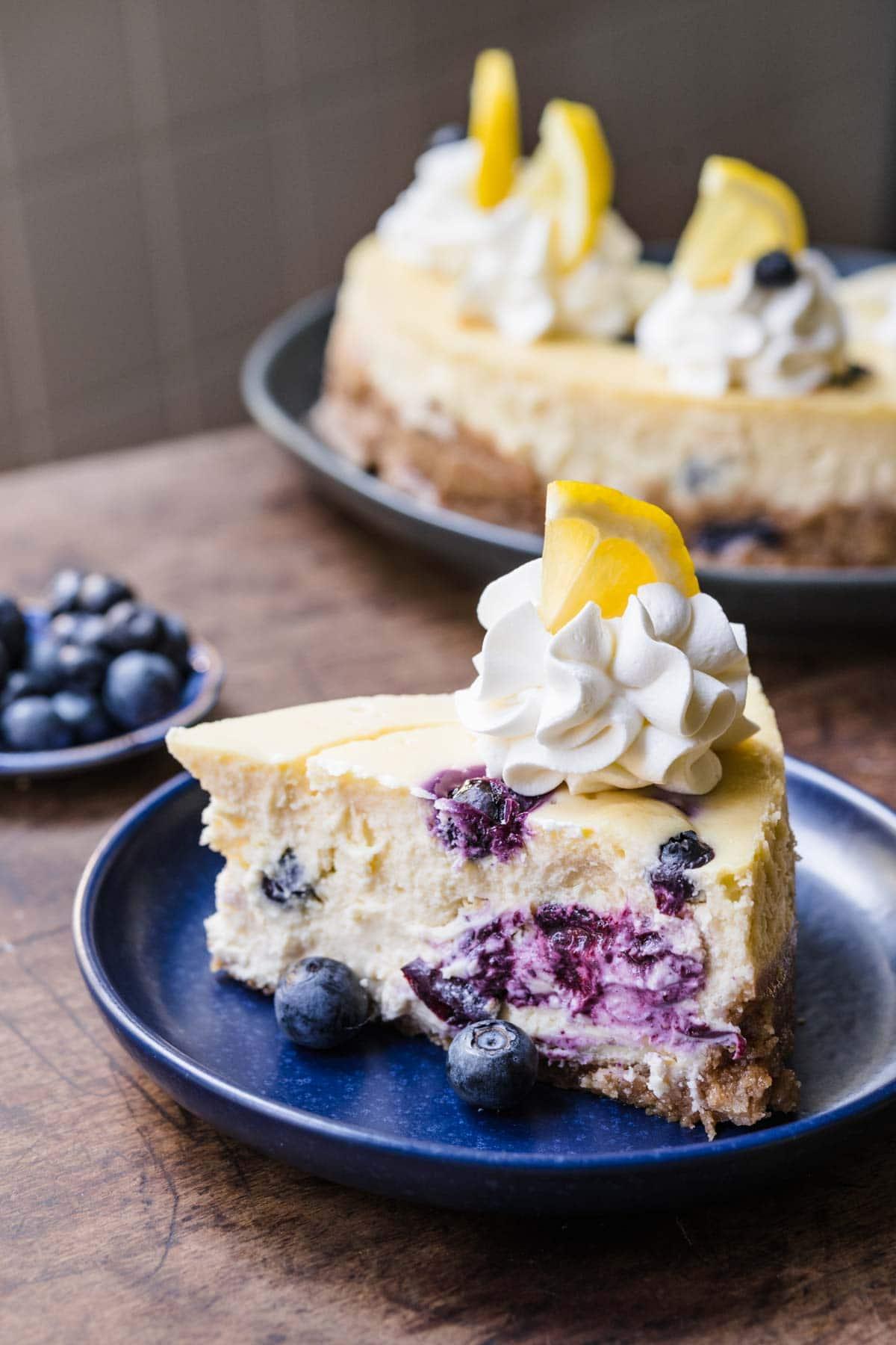 Blueberry Lemon Cheesecake slice on plate with whipped cream, fresh blueberries and lemon garnish