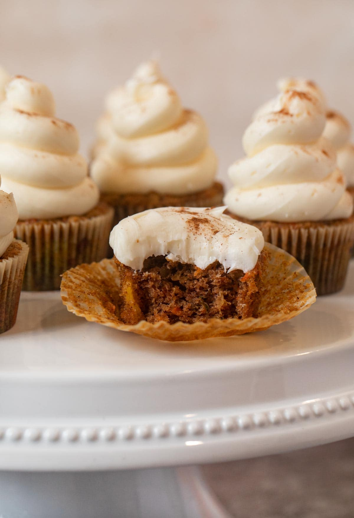 Carrot Cupcake with bite removed on cake stand
