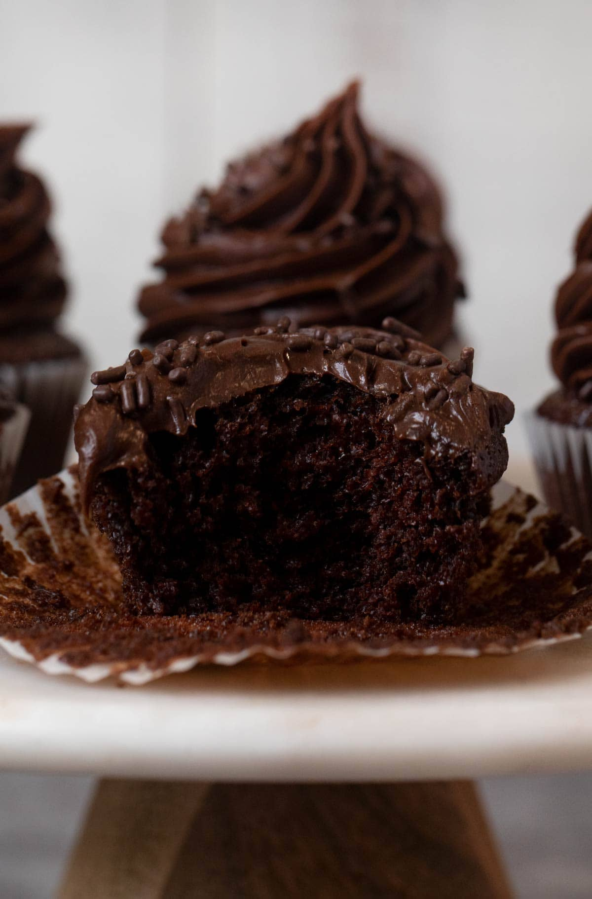 Chocolate Cupcake with Chocolate Frosting and chocolate sprinkles with bite removed