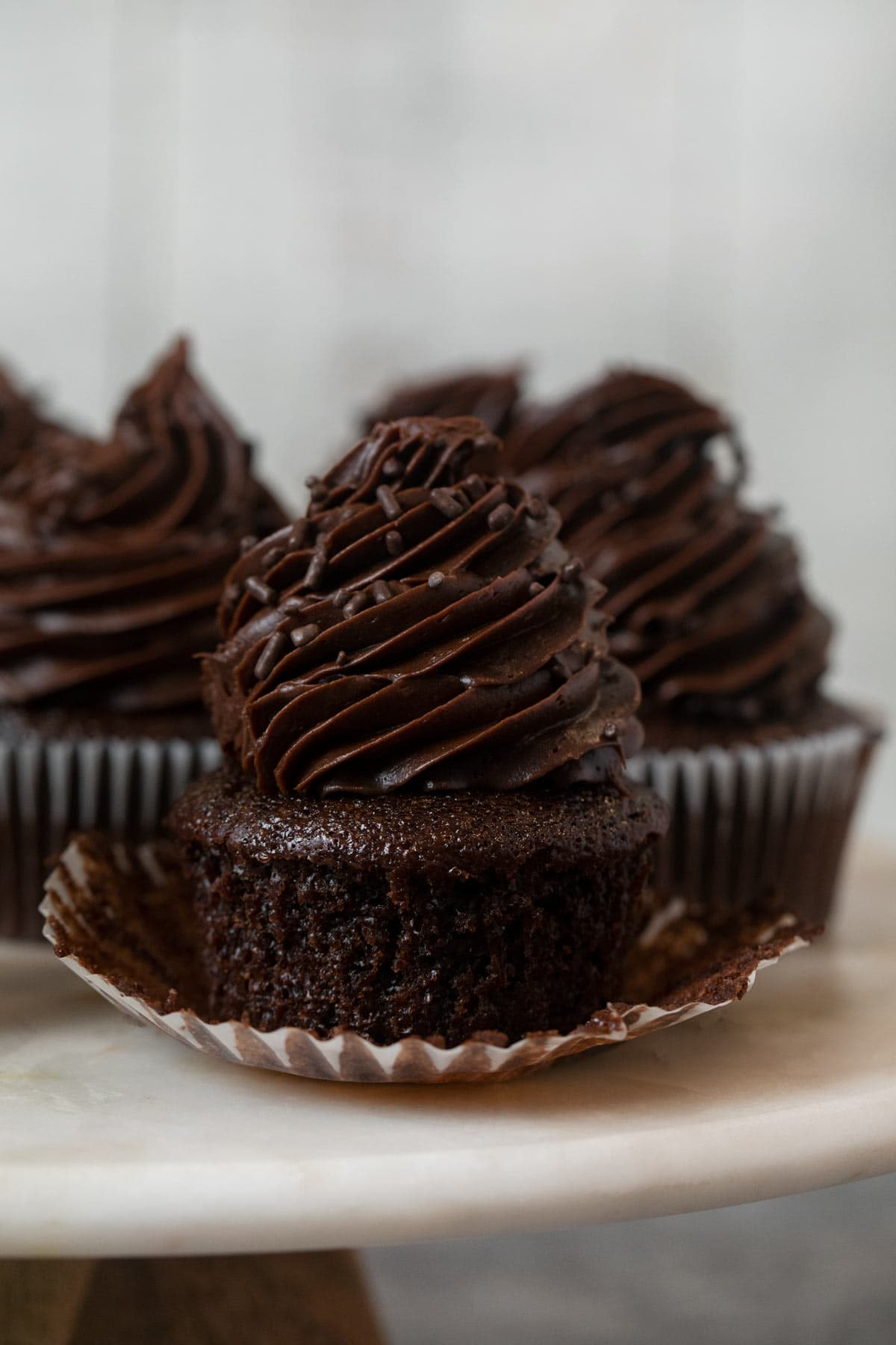 Chocolate Cupcake with Chocolate Frosting on cake stand with cupcake liner removed