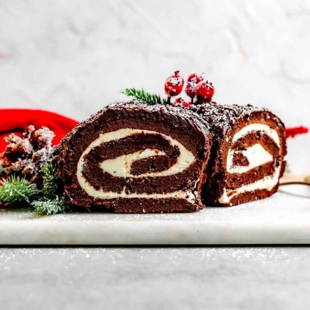 Chocolate Yule Log with powdered sugar and holly garnish