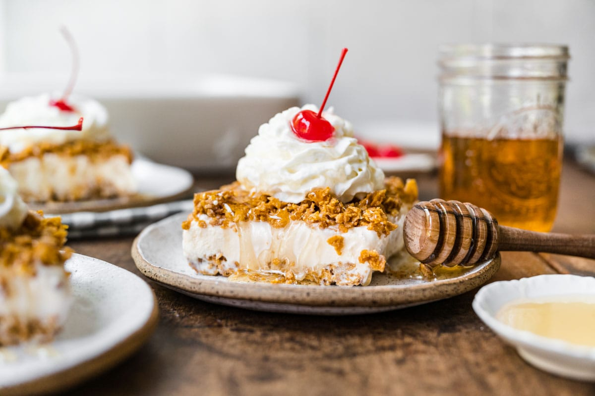 Fried Ice Cream Dessert Casserole slice on plate with whipped cream and cherry on top