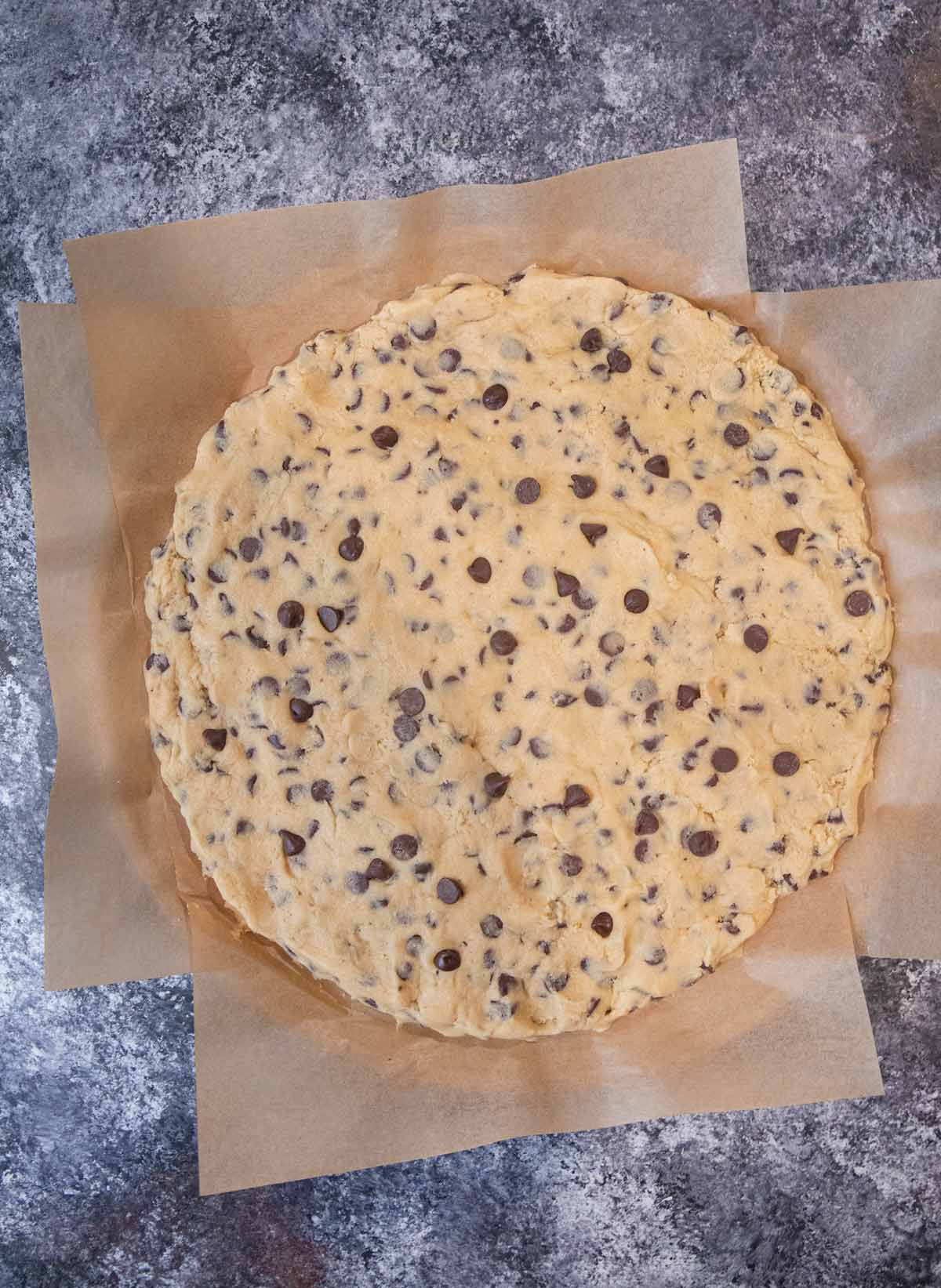 Giant Chocolate Chip Cookie dough on parchment paper