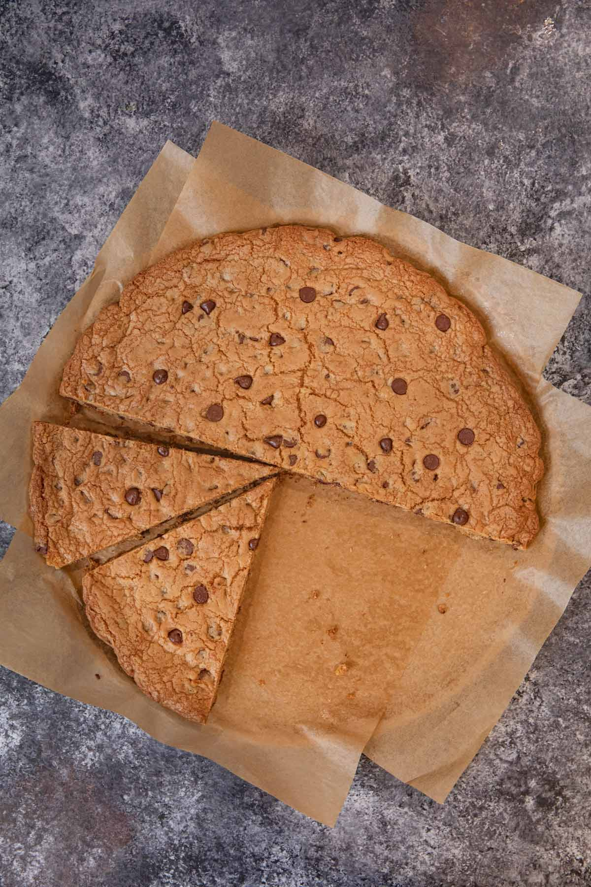 Giant Chocolate Chip Cookie sliced on parchment paper