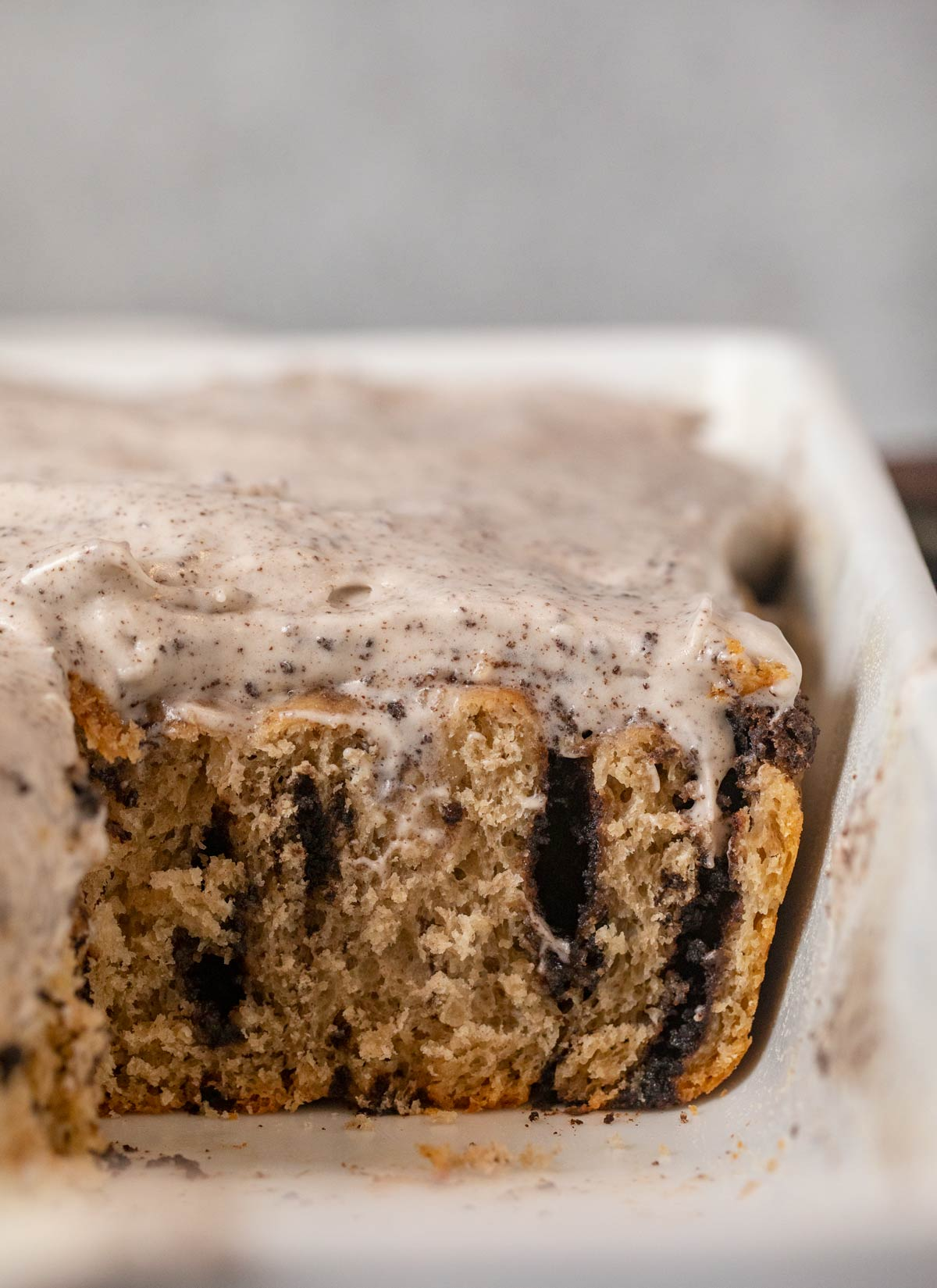 cross-section of Oreo Cinnamon Rolls in baking dish with Oreo frosting