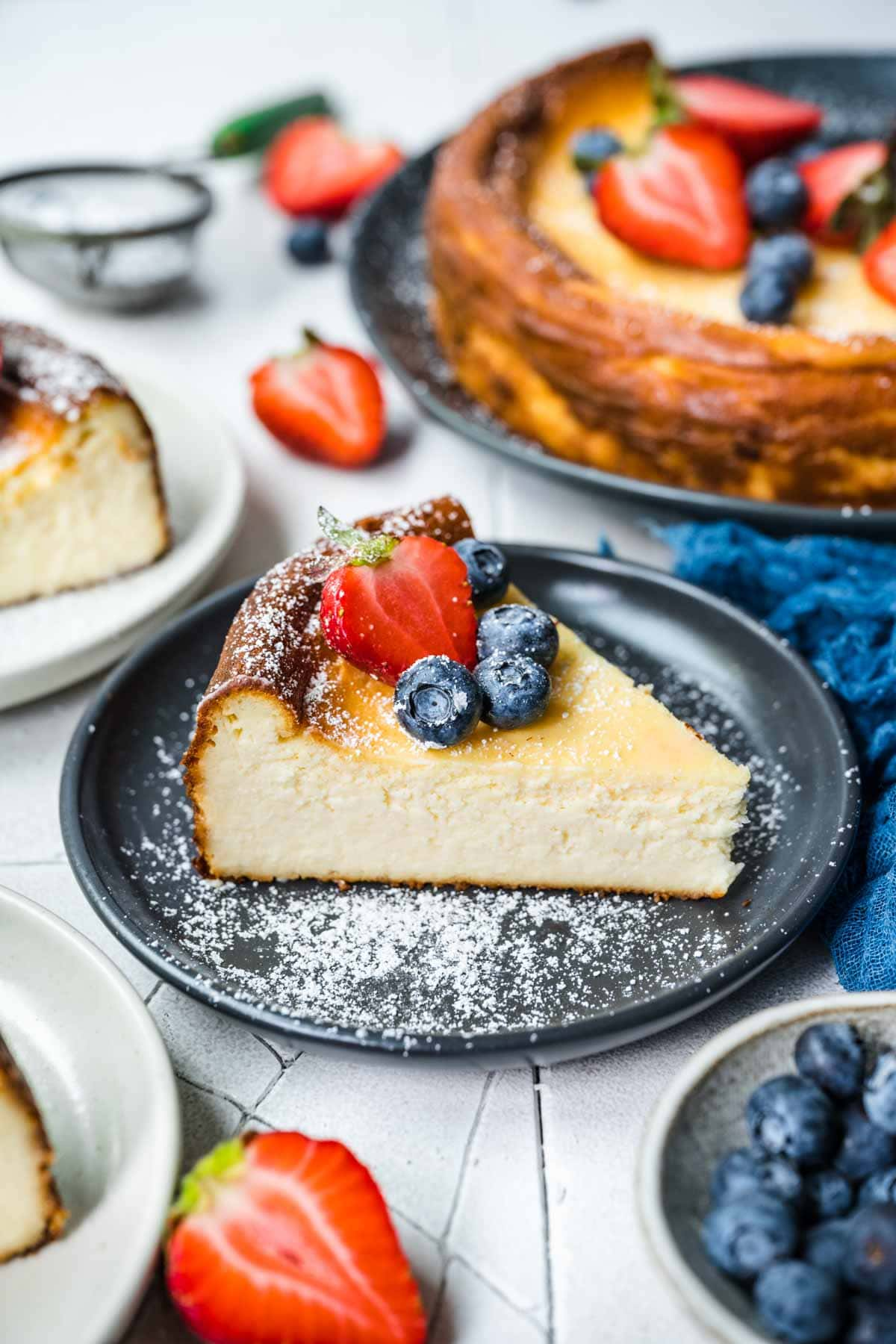 Ricotta Cheesecake slice on serving plate with fresh berries and powdered sugar on top