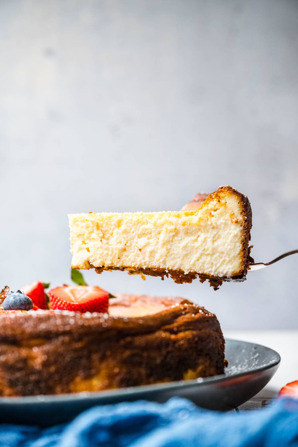 Ricotta Cheesecake side view slice lifted from whole cake
