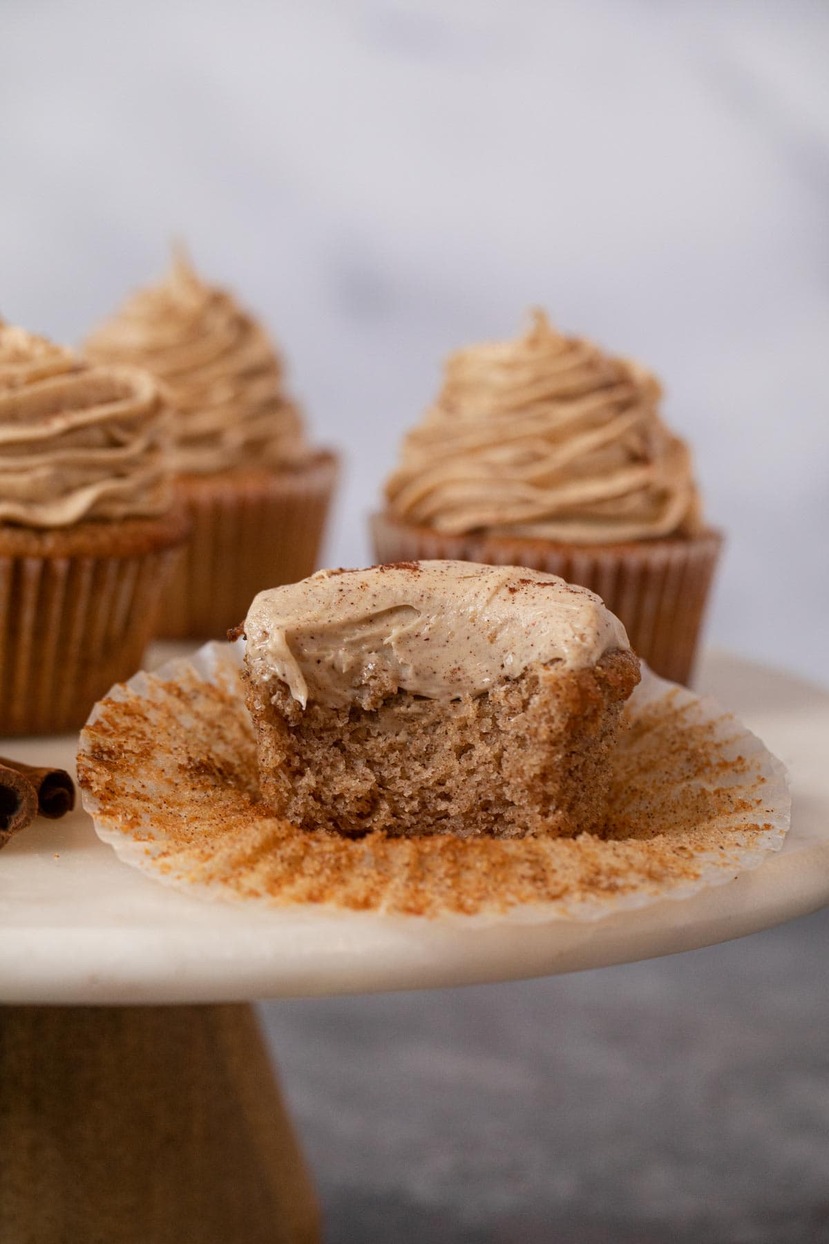 Snickerdoodle Cupcakes with bite removed on cake stand