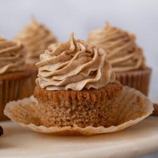 Snickerdoodle Cupcakes with liner removed on cake stand