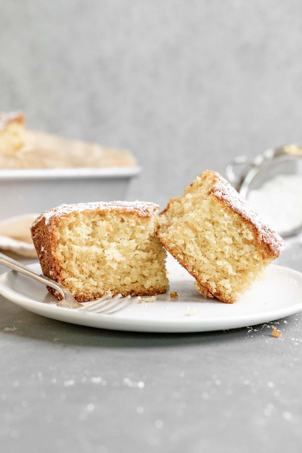 Butter Cake dusted with powdered sugar sliced on plate with fork