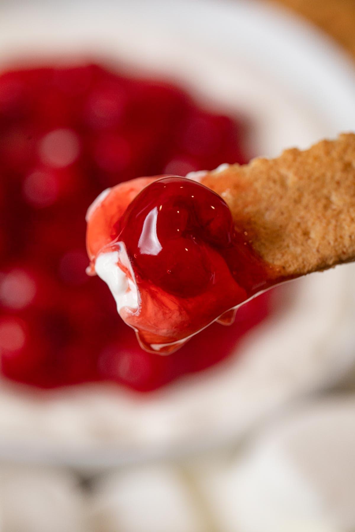 scoop of Cherry Cheesecake Dip on graham cracker dipper