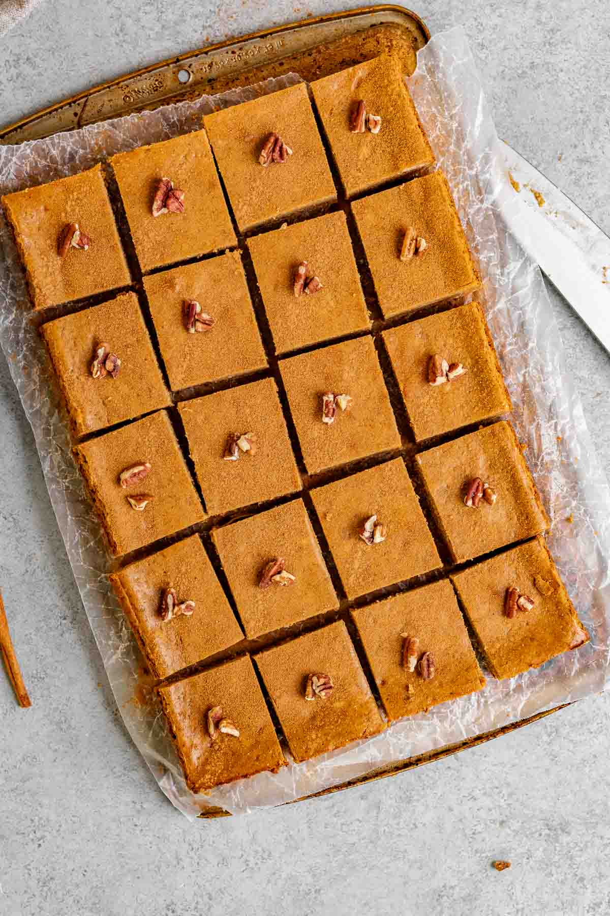 Gingerbread Cheesecake Bars sliced on a board with parchment