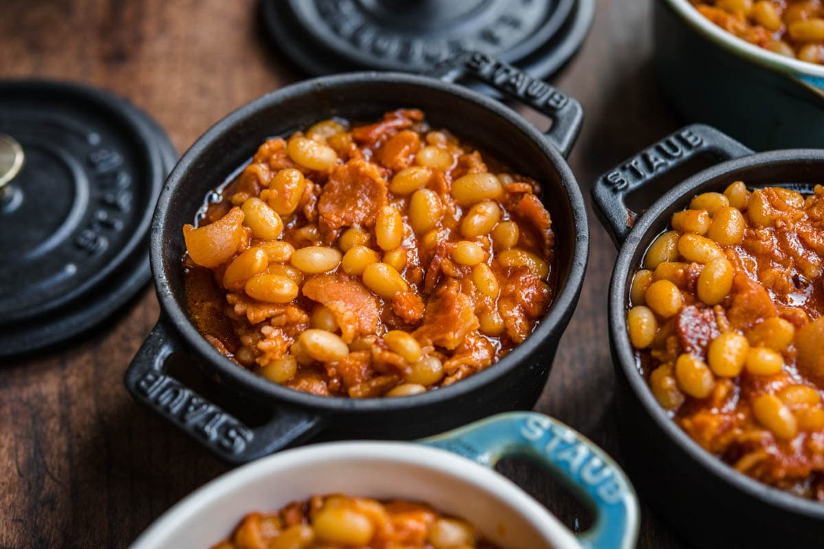 Homemade Pork and Beans with bacon and sauce in small cast iron pots for serving