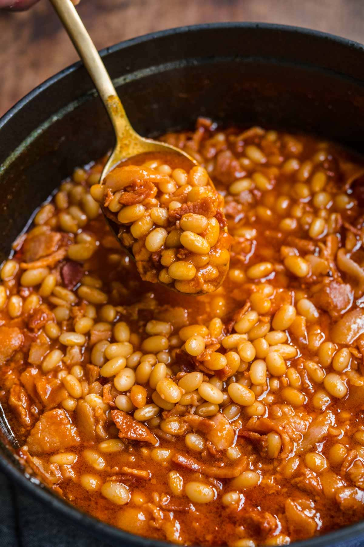 Homemade Pork and Beans with bacon and sauce in pot with spoon