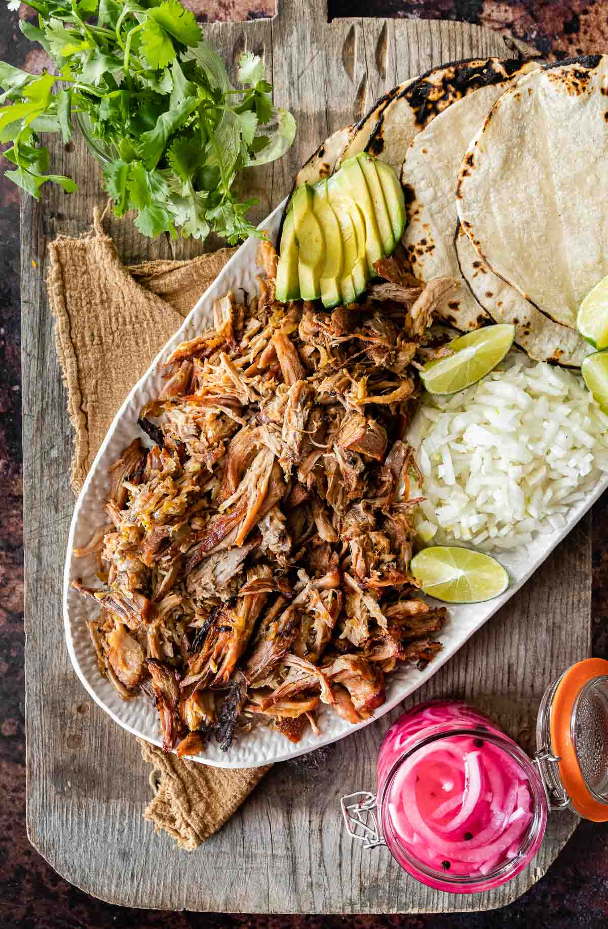 Pork Carnitas (Oven) on serving dish with rice, tortillas, limes, avocado, and pickled onions