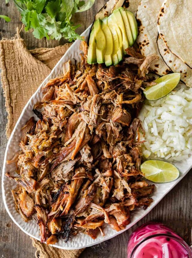 Pork Carnitas (Oven) on serving dish with rice, tortillas, limes, avocado