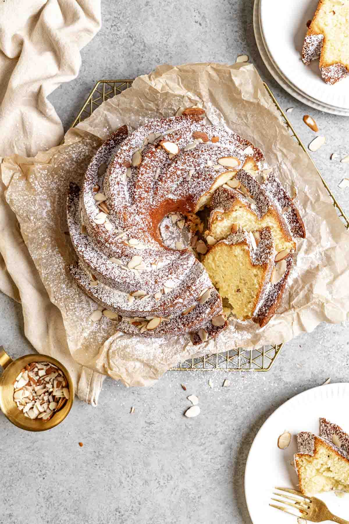 Almond Bundt Cake dusted with powdered sugar and sliced on parchment