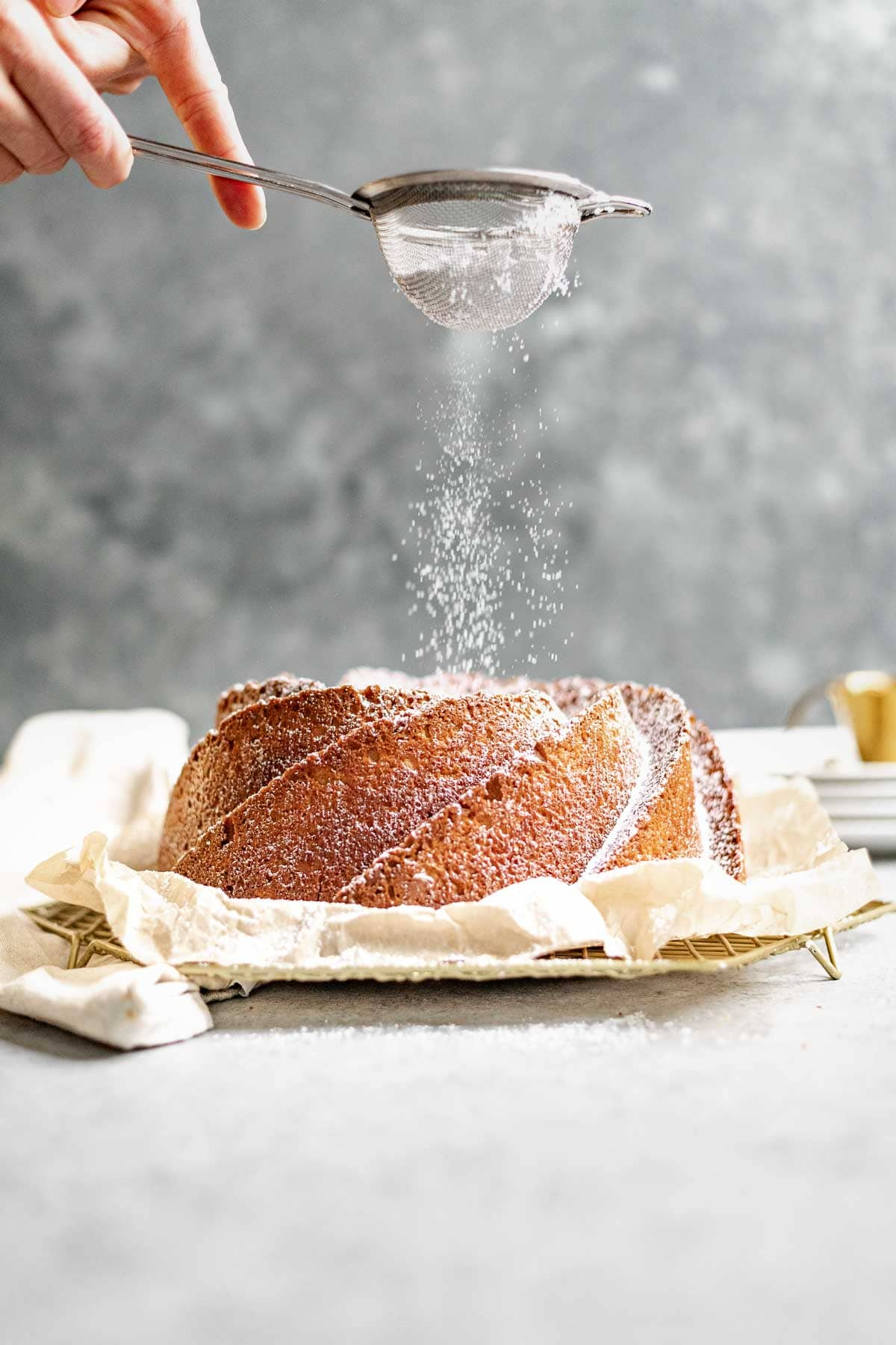 Almond Bundt Cake dusted with powdered sugar on parchment