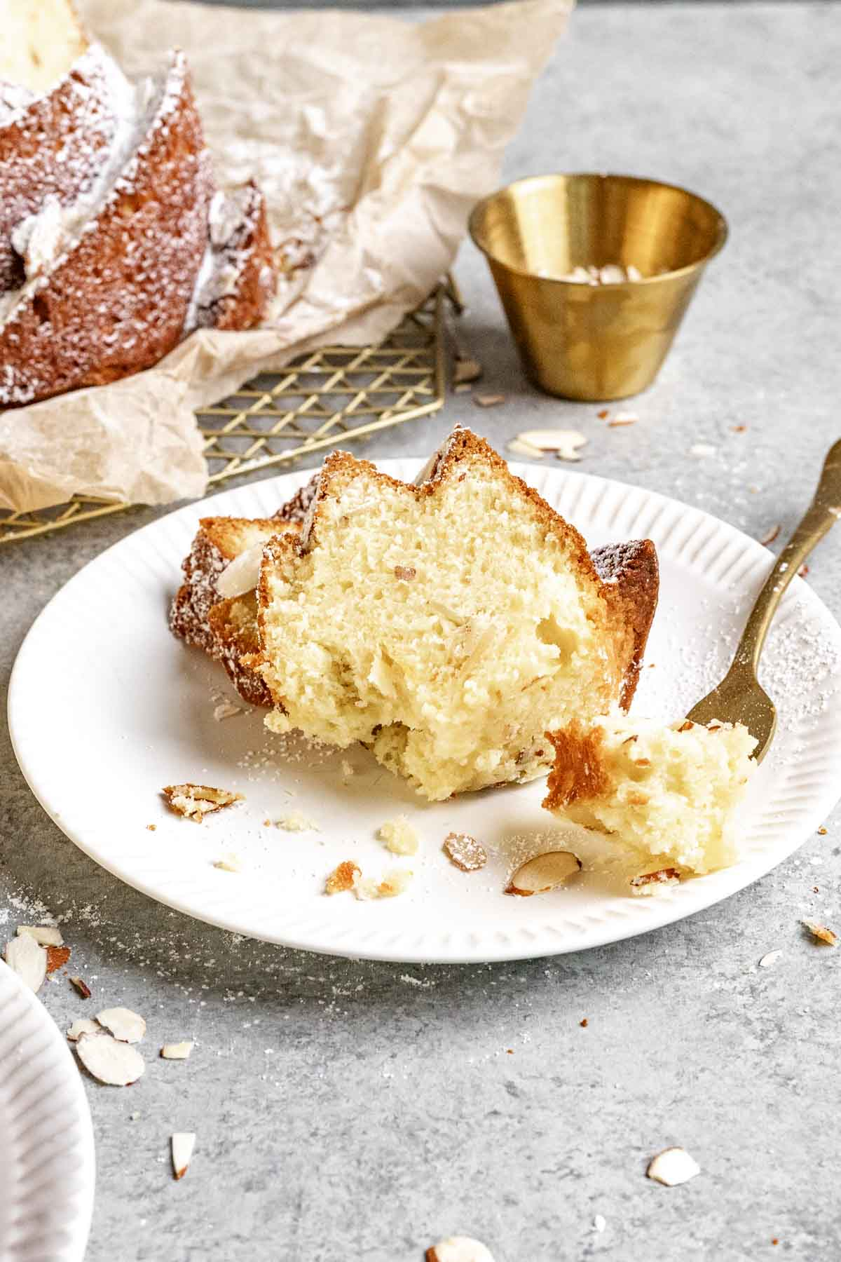 Almond Bundt Cake dusted with powdered sugar sliced on plate