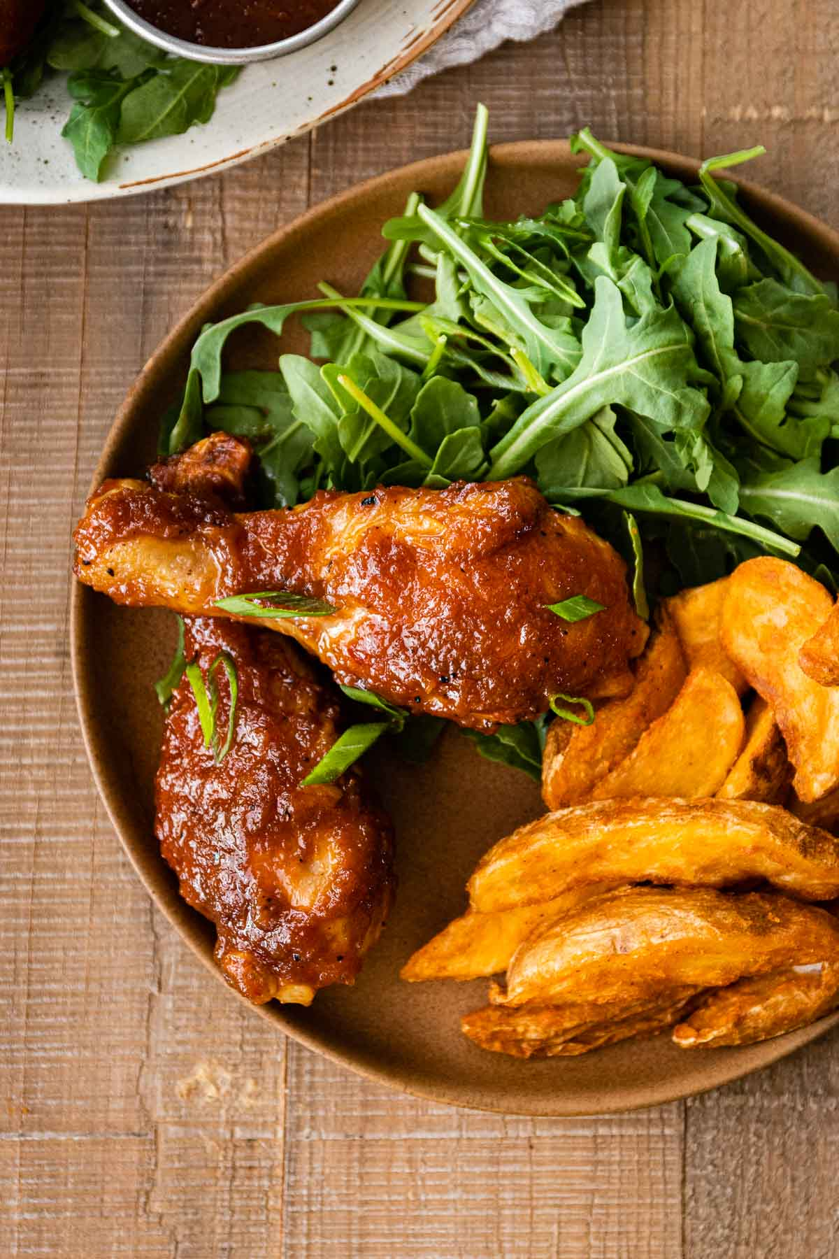 Applesauce BBQ Chicken on dinner plate with arugula salad and potato wedges