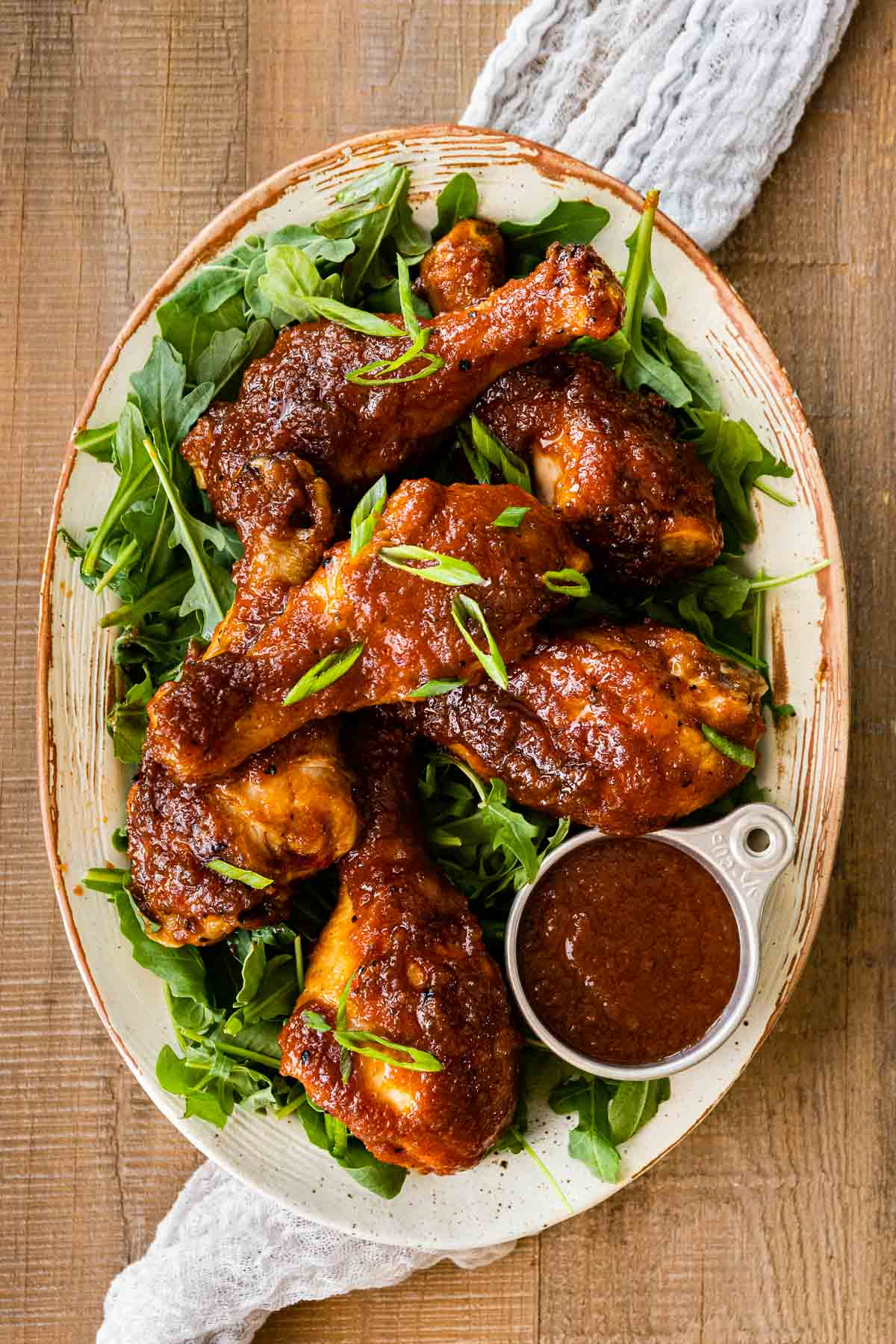 Applesauce BBQ Chicken on serving plate atop arugula and garnished with sliced green onions