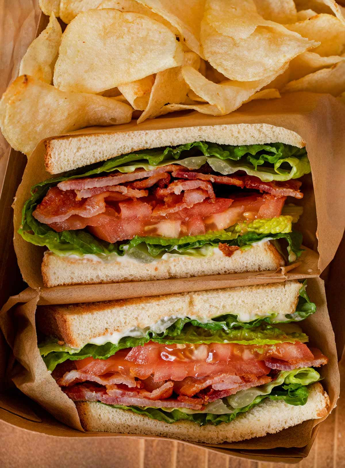 BLT Sandwich sliced in half with chips