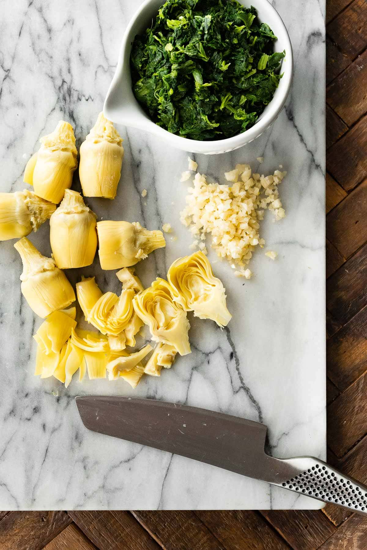 Artichokes on cutting board for Baked Spinach Artichoke Chicken