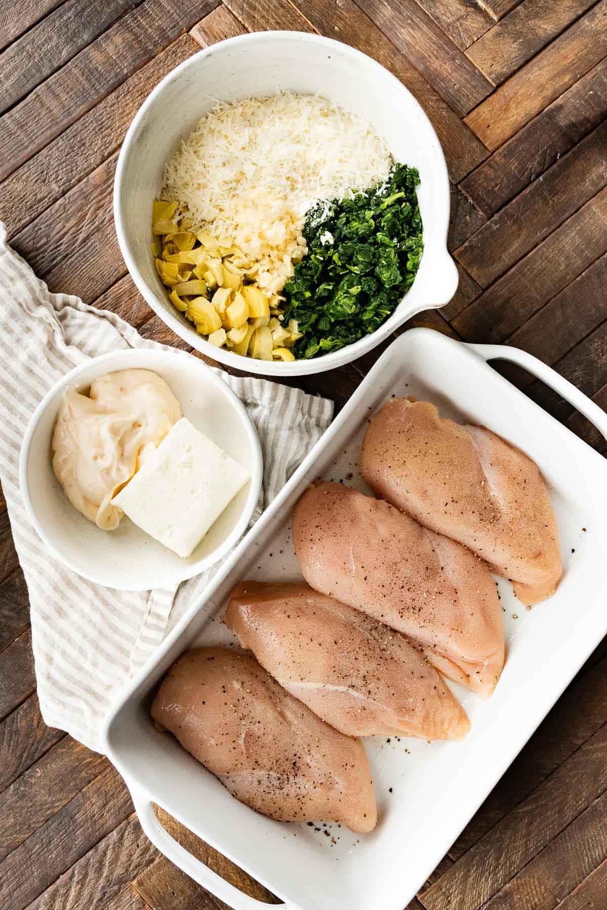 Chicken in baking dish and topping ingredients for Baked Spinach Artichoke Chicken
