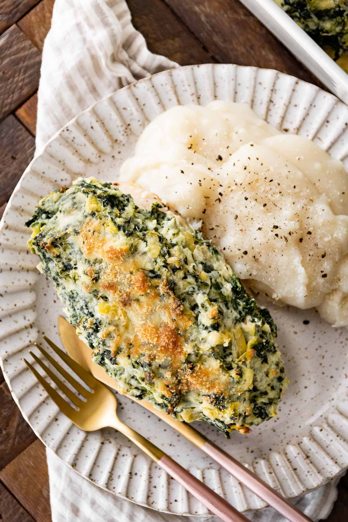 Baked Spinach Artichoke Chicken on plate with mashed potatoes