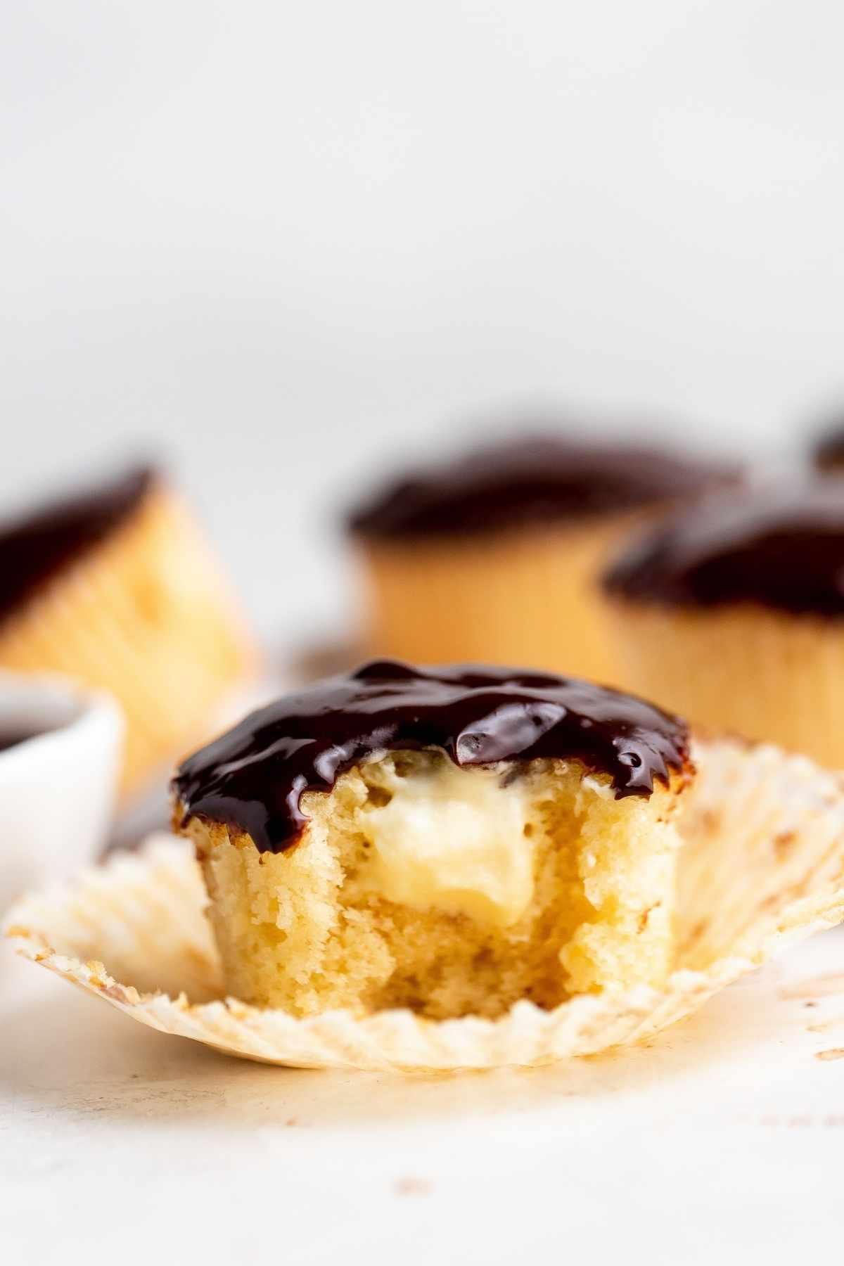 Boston Cream Cupcakes vanilla cupcake with bite exposing cream filling and chocolate ganache frosting