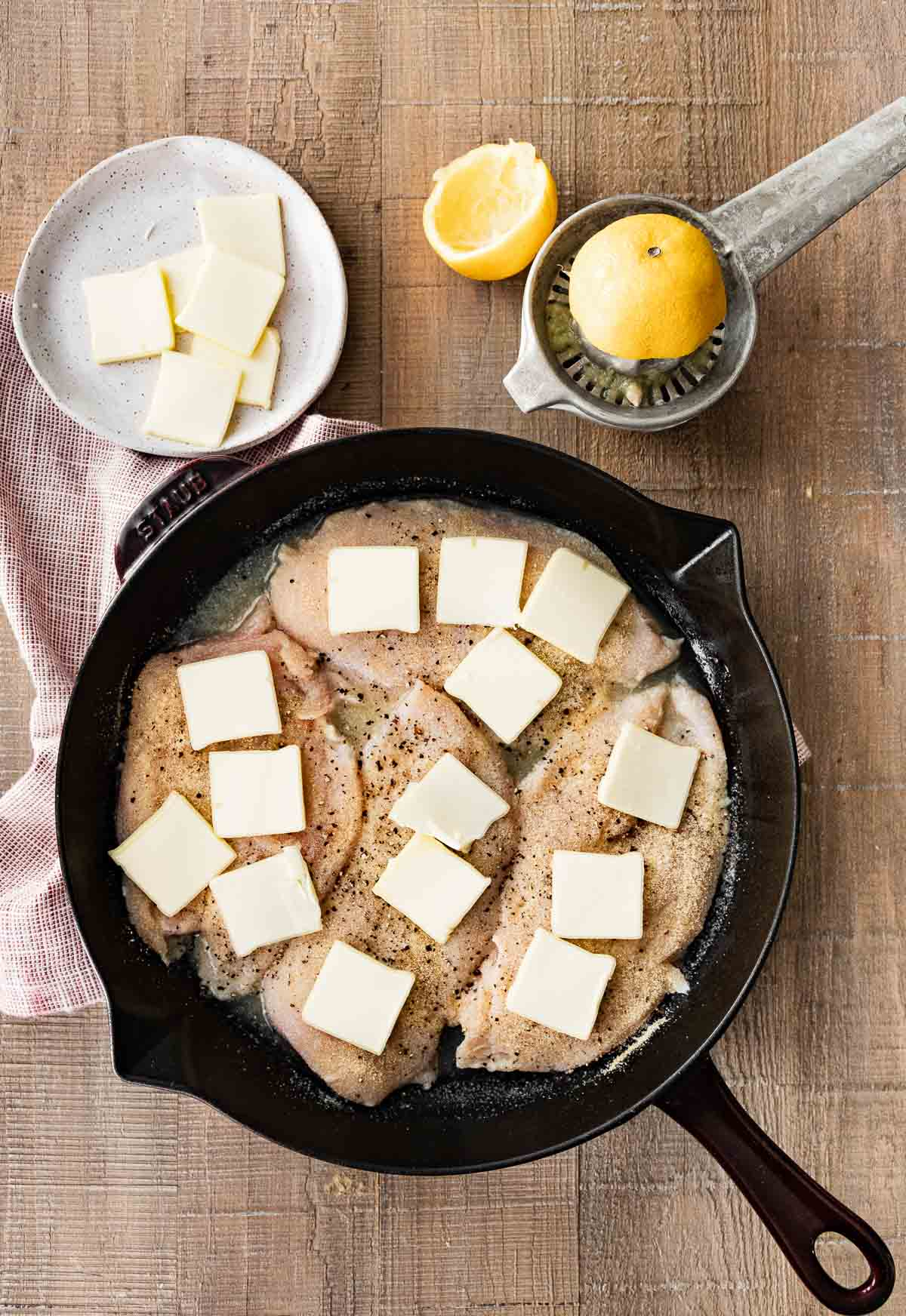 Buttery Lemon Garlic Baked Chicken in pan with butter