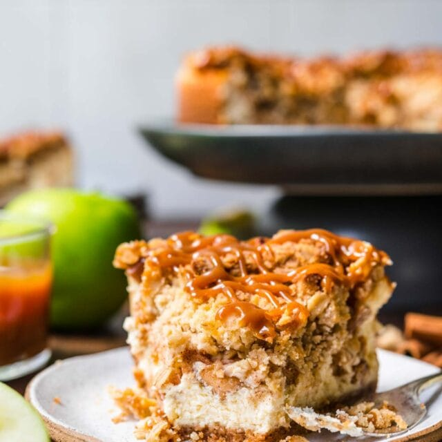 Caramel Apple Crumb Cheesecake slice on plate with caramel drizzle on top and fork